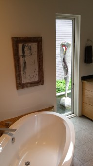 Soaking tub with view of sculpture in courtyard