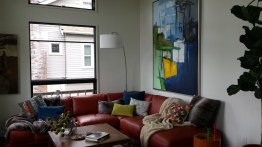 Two-story living room with red couch and modern art