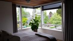 Corner windows and wood ceiling in master bedroom.