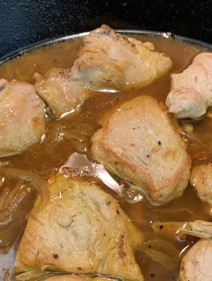 Chicken breast pieces in a skillet with gravy.