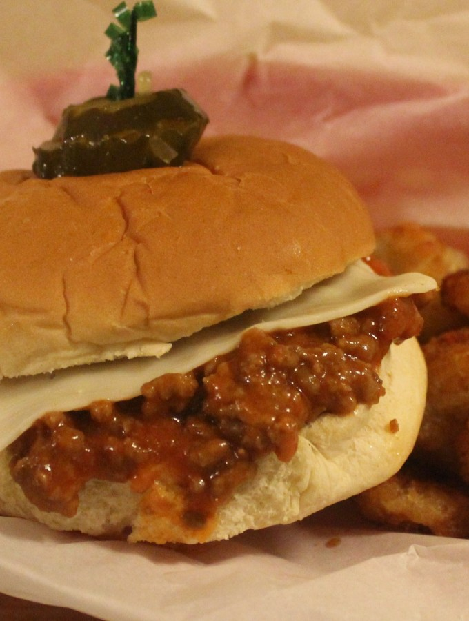 Sloppy Joe on a bun with cheese and pickles on a toothpick. It is on a parchment paper lined basket with round potatoes.