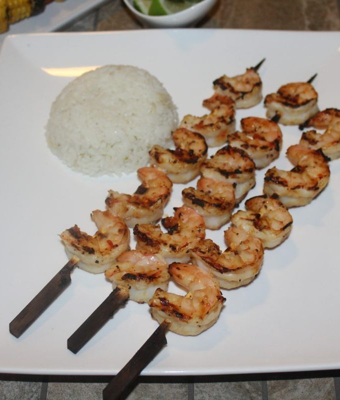 A square white plate with 3 skewers of grilled shrimp and a side of rice next to it.