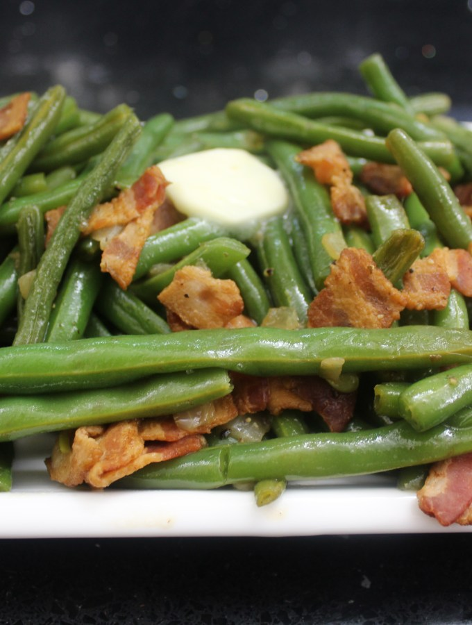 Green beans with bacon and onions on a white glass plate with a pad of butter on top