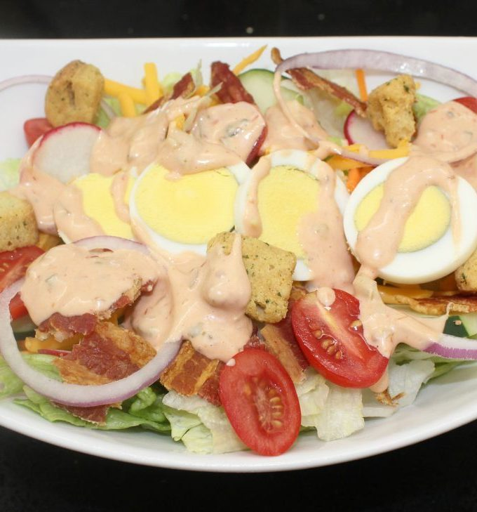 A salad with lettuce, tomatoes, red onions, bacon, and hard boiled eggs on a white plate with thousand island drizzled on it.