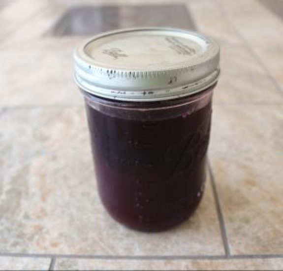 A mason jar filled with berry agave syrup.