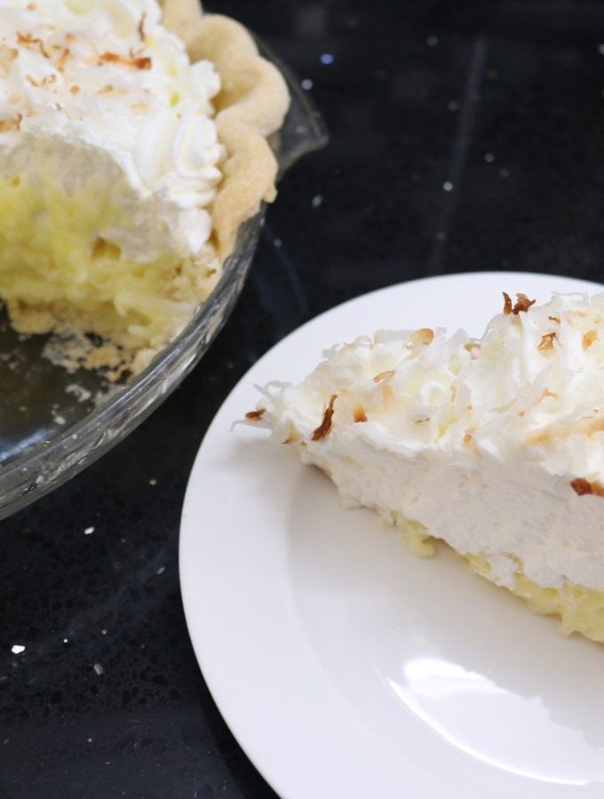 A slice of coconut cream pie along side a cropping of the remainder of the pie