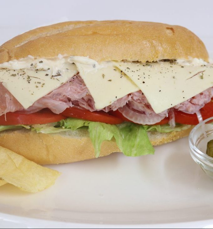 A Hoagie filled with lettuce, tomatoes, onions, ham, cheese, oregano, and mayonnaise with a side of chips and pickles