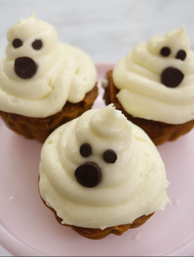3 ghostly pumpkin cupcakes on a pink cake tray.