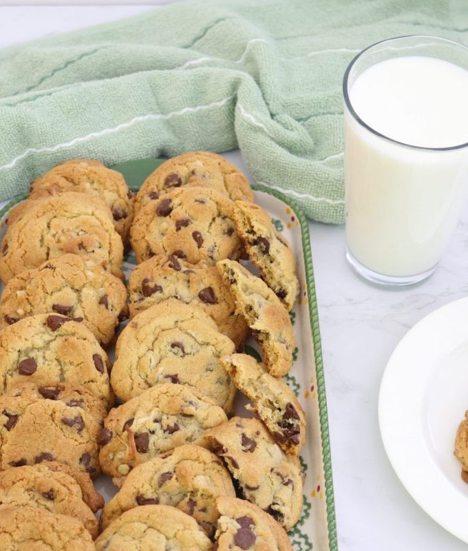 green platter of chocolate chips with glass of milk and plate of cookies