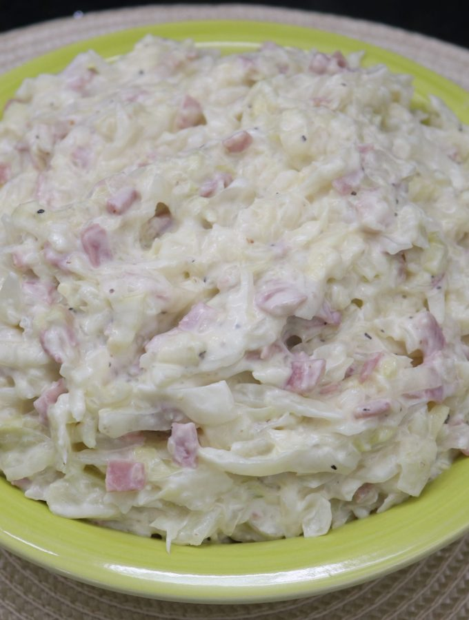 A green bowl filled with creamed cabbage and ham