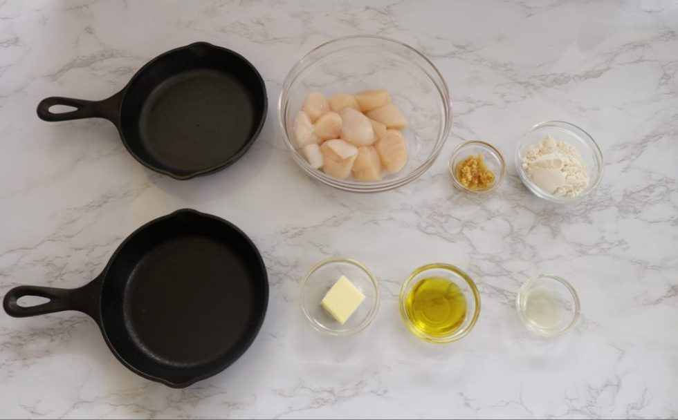 2 small cast iron skillets with a few small glass bowls of scallops, olive oil, butter, lemon juice, and minced garlic