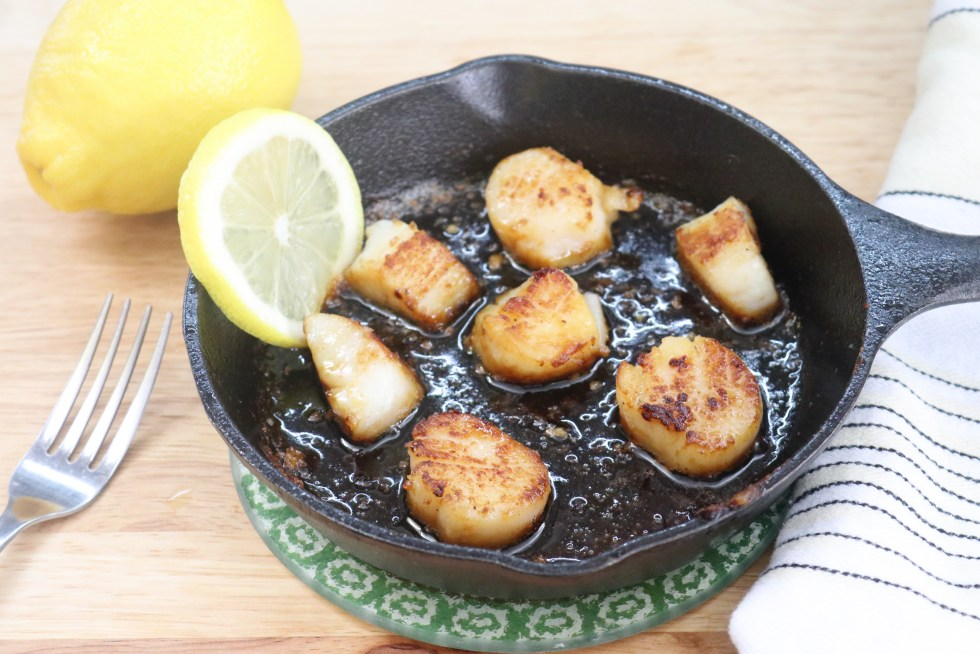 small cast iron skillet with cooked scallops and a slice of lemon on a brown surface