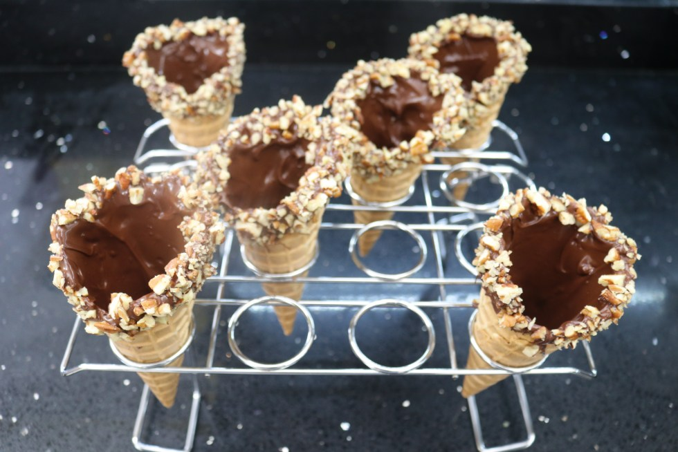 Metal rack of 6 chocolate dipped waffle cones with nuts