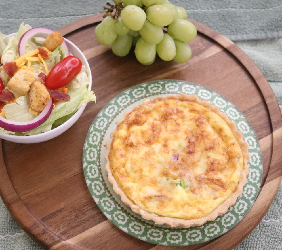 Small Brunch Quiche tart on a round wooden board with side salad and green grapes