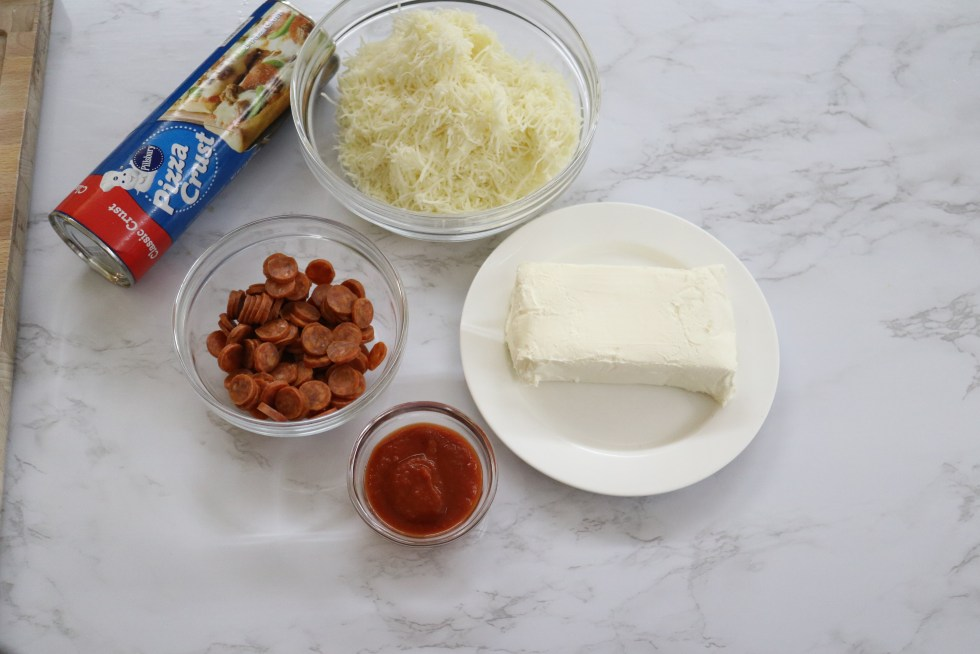 Ingredients for pizza pinwheels, pizza dough, mozzrell cheese, cream cheese, small pepperoni, and marina sauce