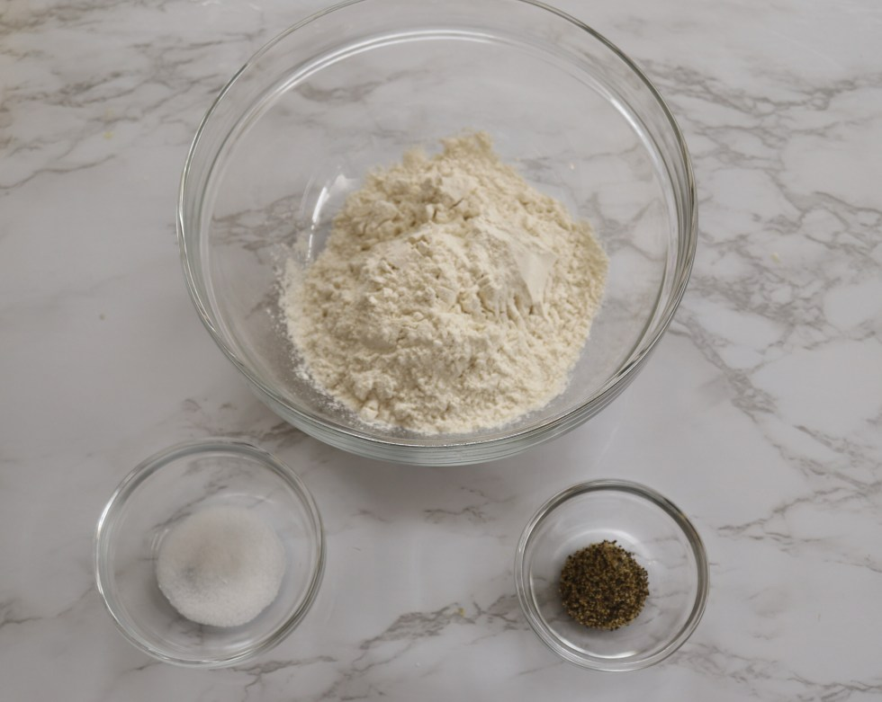 large bowl of flour and 2 smaller of salt and pepper