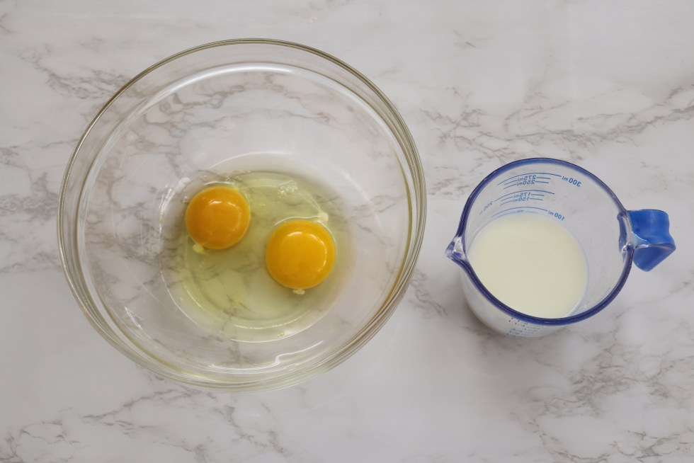 a bowl with 2 eggs and a measuring cup with milk