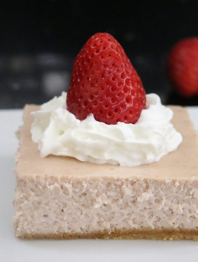 Strawberry Cheesecake Bar on square plate with strawberries