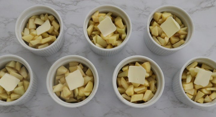 Chopped apples in ramekins with butter
