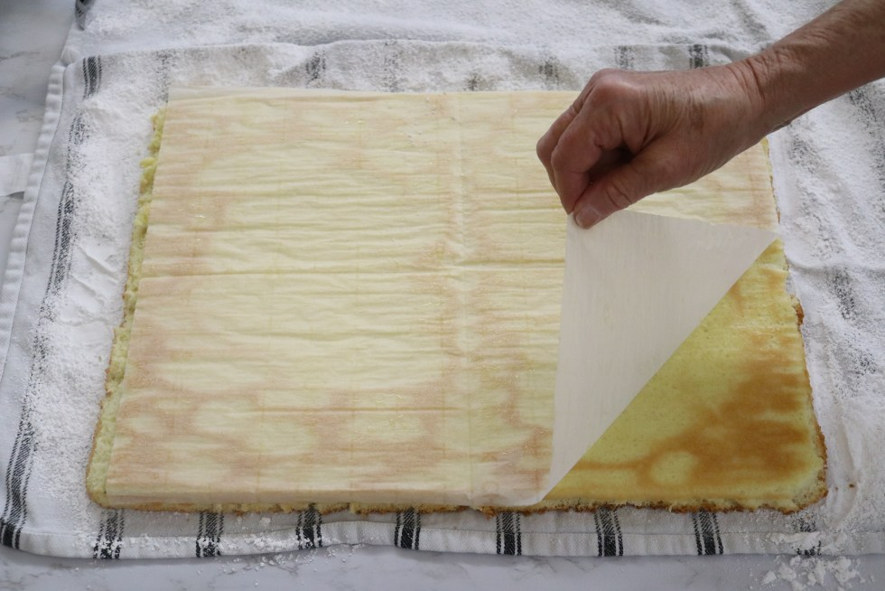 Peeling parchment paper back from cooked cake
