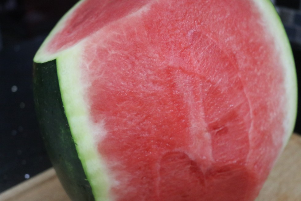 Watermelon with half of rind off of watermelon
