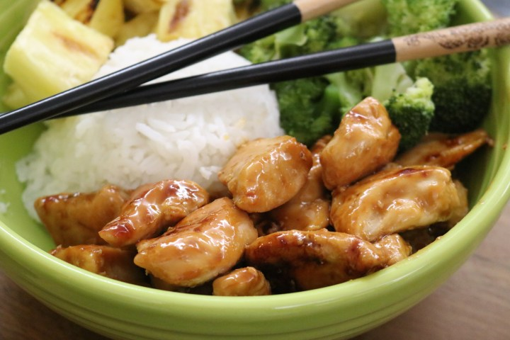 A bowl of teriyaki chicken with broccoli, pineapple, and rice.