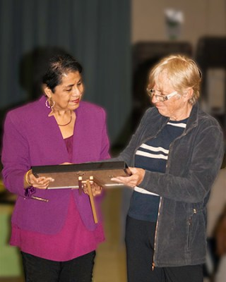 President and Co-founder Catherine Gillbert accepts volunteer recognition certificate from outgoing Coordinator Perveen Khokhar