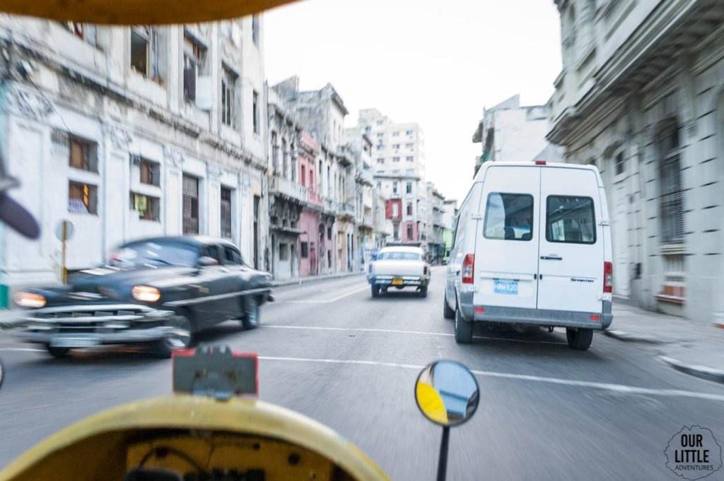 Ulica w Hawanie podczas jazdy Coco taxi. Widoczna prędkość i mijane stare samochody