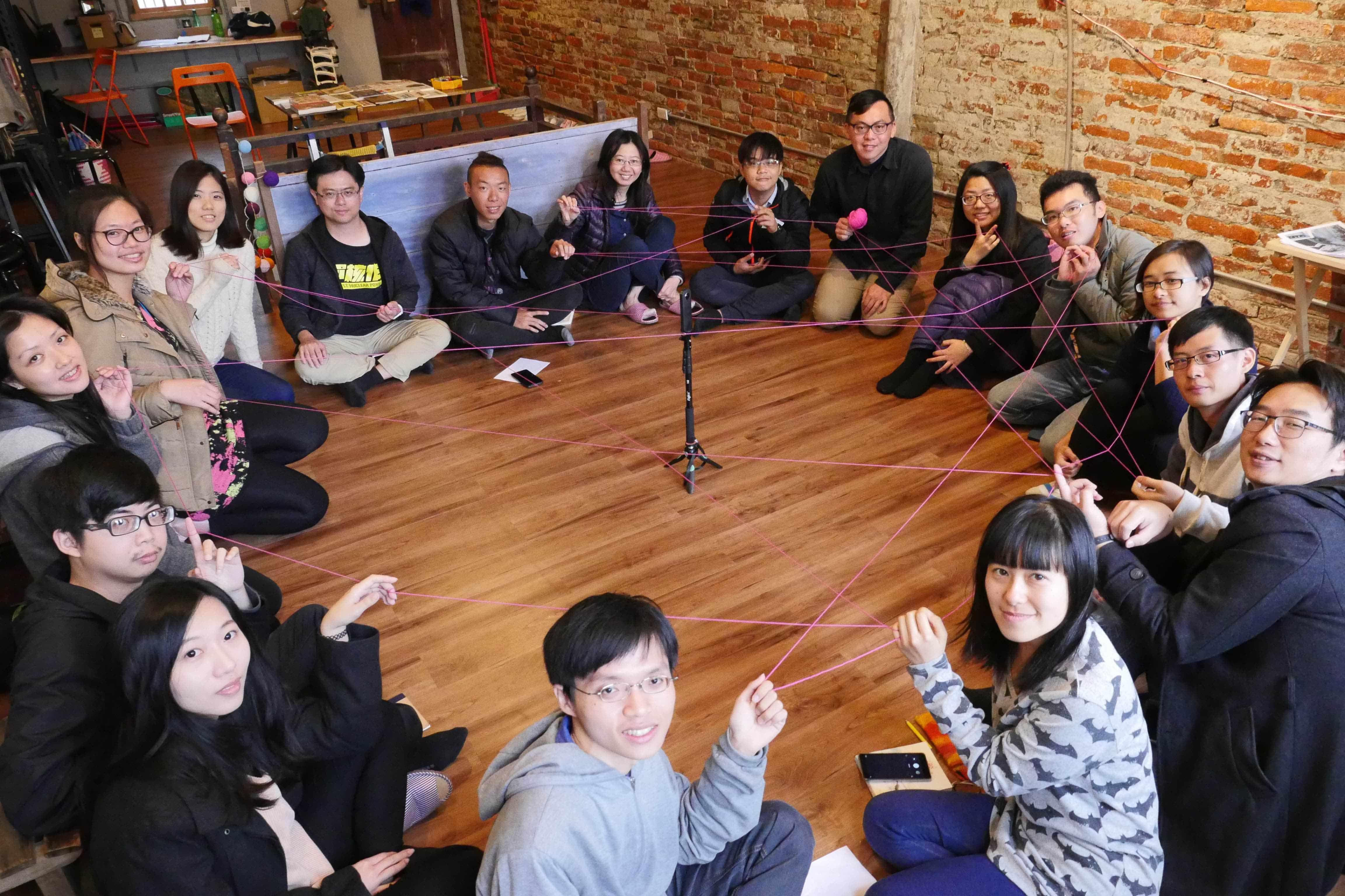 一群人在橫街工作室地板上拉毛線圓圈