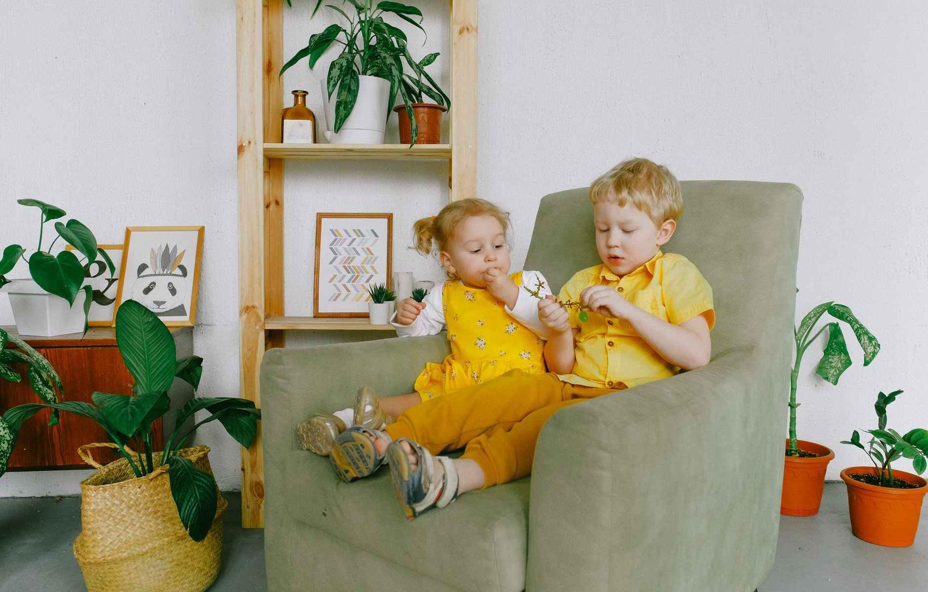 a photo of siblings eating grapes