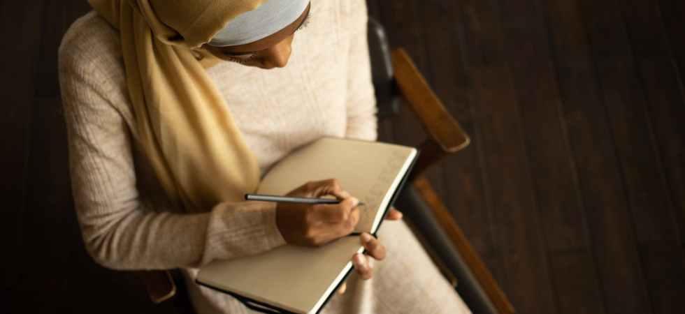 crop black muslim woman writing in planner