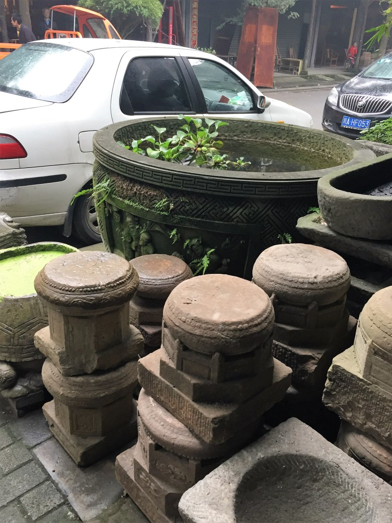 Stone pots, pedestals and ornaments - presumably antique - for sale.