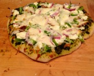 Kylie's pizza with homemade pesto, homemade ricotta, grilled chicken, red onion, green pepper, and mozzarella.