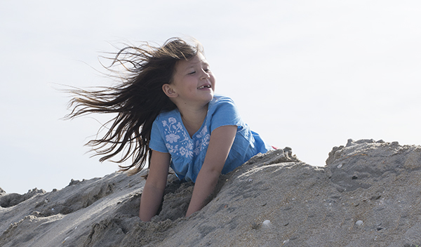 girl playing in sand dune