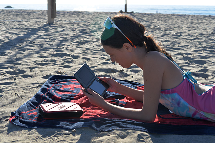 girl-playing-nintendo-3ds-at-beach