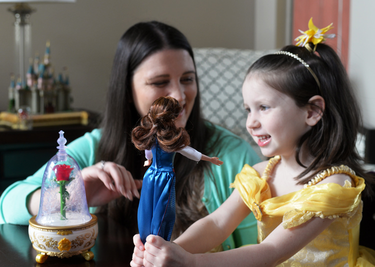 kid playing with belle doll