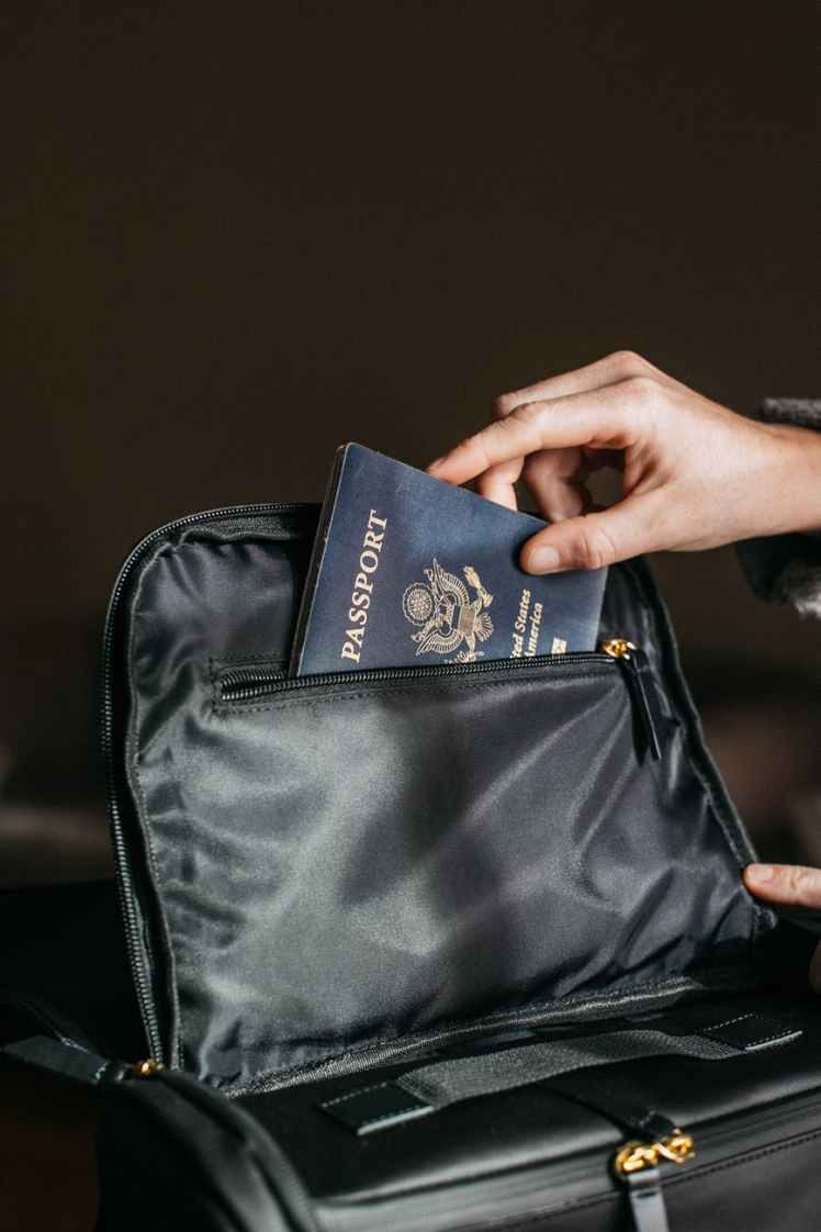 person putting a passport on bag