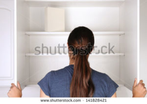 stock-photo-closeup-of-a-woman-looking-in-an-empty-pantry-seen-from-behind-there-is-only-one-box-of-food-141828421