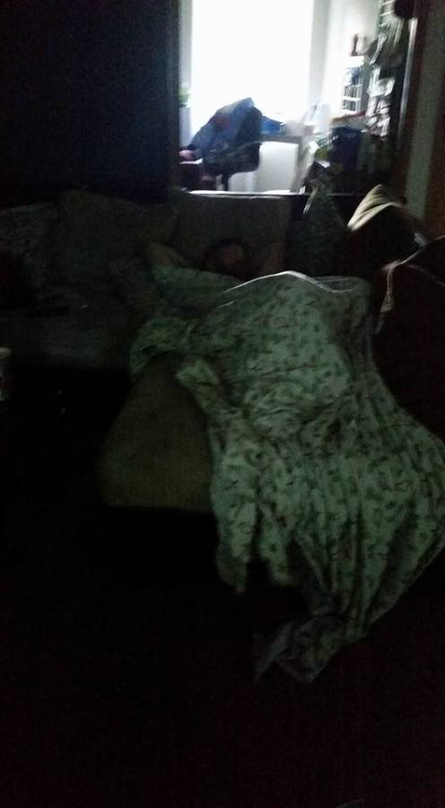 My Husband sleeping on the couch across from my chair.