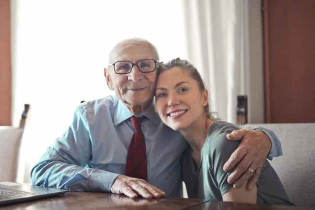 positive senior man in formal wear and eyeglasses hugging with young lady while sitting at table