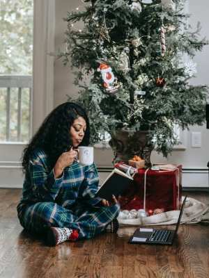 calm black woman drinking coffee and reading book