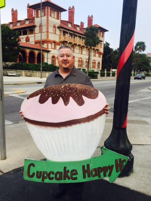 I am an unemployed Army veteran standing on a street corner holding a cupcake sign just to make money