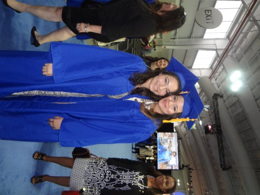 Two young smiling  women in graduation caps and gowns.
