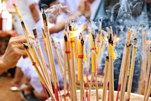 many incense sticks on a bowl of sand