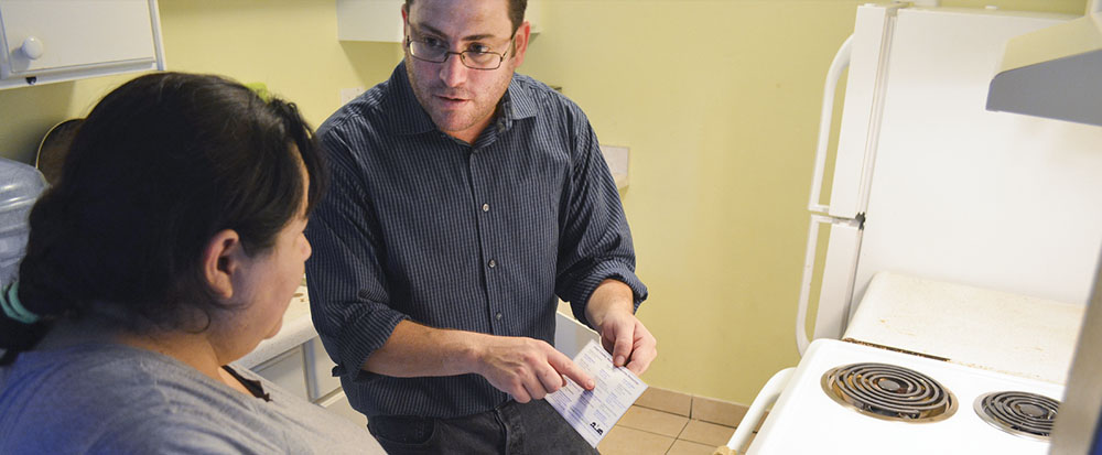 Pest control technician talking to tenant