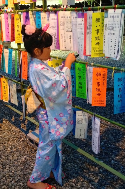 Young girl in her Yuakata placing her Tanzaku (wish)