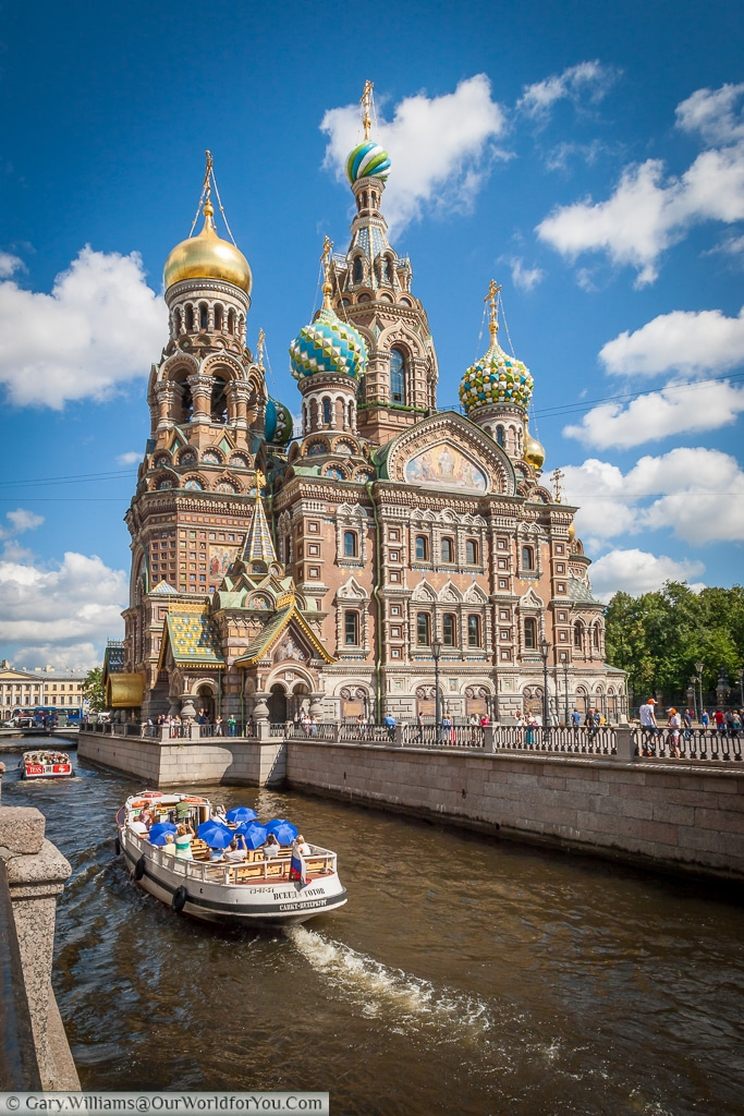 A pleasure boat passes the Church of the Savior on Spilled Blood on the Moyka River, St Petersburg, Russia