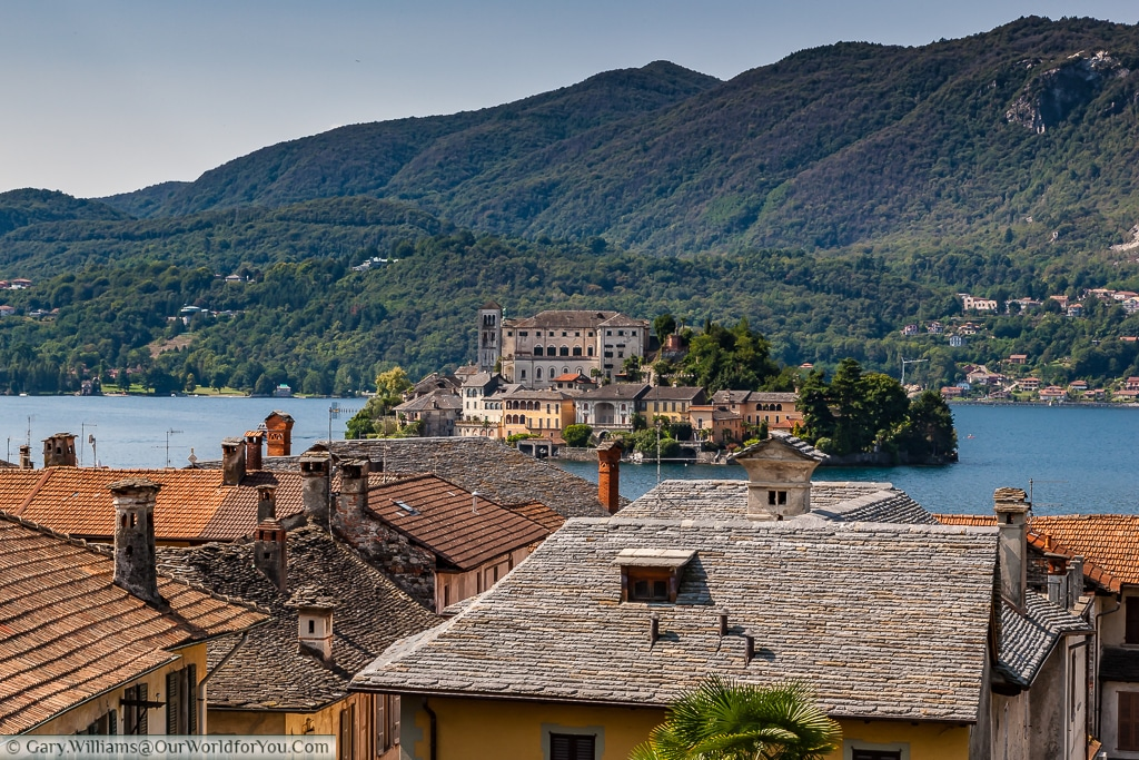 A view across the roof tops to Isola San Giulio from Orta San Giulio , Lake Orta, Italy