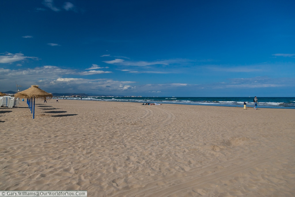 The golden sands and blue sky of the Malvarrosa Beach, Valencia, Spain