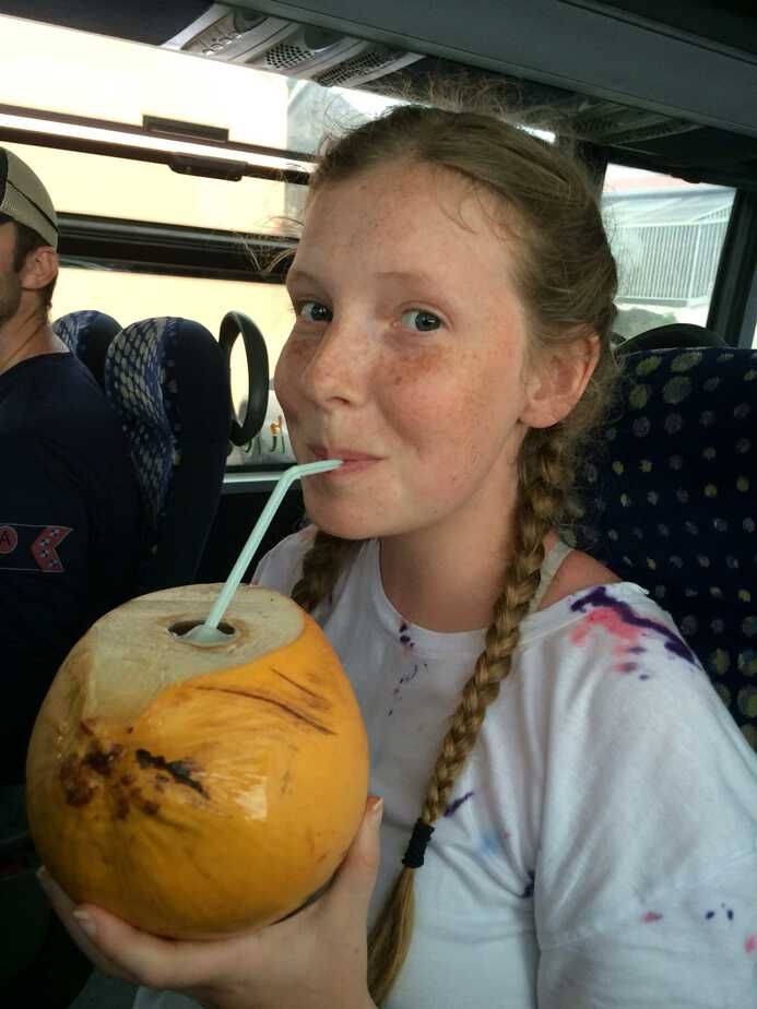 Sarah drinking a coconut on the bus in Guadeloupe.